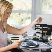 Mujer en su oficina de casa frente a un ordenador revisando unos papeles