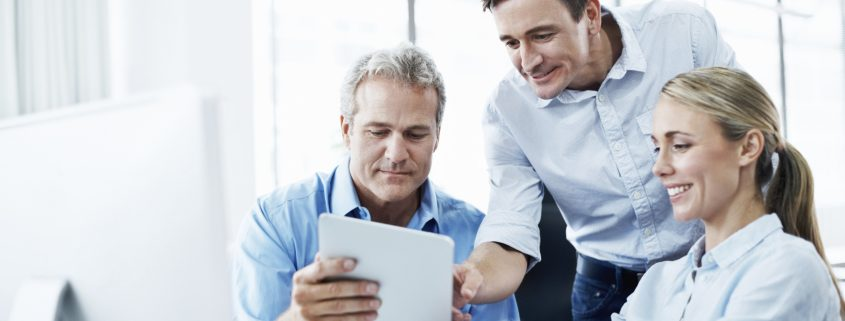 three businesspeople looking at a digital tablet while working together in their office 2
